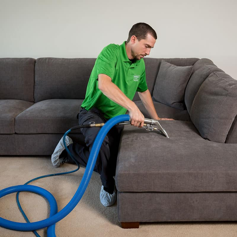 Refresh Carpet Cleaning employee vacuuming the couch