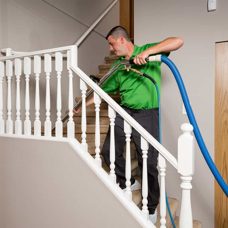 A Refresh Vancouver carpet cleaning employee doing some steam cleaning on the stairs